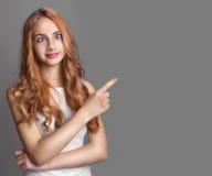 Retrato de una muchacha bonita que señala el finger lejos Imagen de archivo libre de regalías
