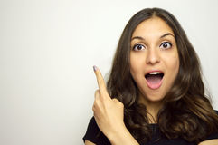 Retrato de una muchacha bonita que señala el finger lejos aislado en un fondo blanco Imagen de archivo libre de regalías