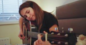 Retrato de una muchacha carismática del adolescente que juega en una guitarra en su sensación del dormitorio grande disfrutando d almacen de video