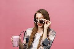 Retrato de una muchacha casual linda que bebe el zumo de naranja de un vidrio y que mira la cámara aislada sobre fondo rosado fotos de archivo