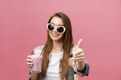 Retrato de una muchacha casual linda que bebe el zumo de naranja de un vidrio y que mira la cámara aislada sobre fondo rosado fotografía de archivo libre de regalías