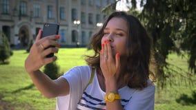 Retrato de una muchacha caucásica sonriente de los jóvenes que se coloca en el parque y que usa un smartphone, haciendo el selfie almacen de metraje de vídeo