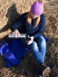 Retrato de una muchacha cerca de un pajar que vierte una bebida de una botella de termo imágenes de archivo libres de regalías