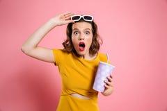Retrato de una muchacha chocada en las gafas de sol que sostienen la taza Foto de archivo