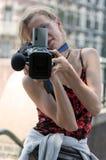 Retrato de una muchacha con una cámara de vídeo imagen de archivo