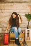 Retrato de una muchacha con de largo, pelo rizado, natural Maleta roja Imágenes de archivo libres de regalías