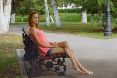 Retrato de una muchacha con el eyesGirl grande y hermoso que se sienta en un banco de parque Fotografía de archivo libre de regalías