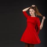 Retrato de una muchacha con el pelo largo en un vestido rojo Fotografía de archivo