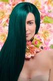 Retrato de una muchacha con el pelo verde en fondo floral Foto de archivo