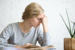 Retrato de una muchacha con exceso de trabajo joven del estudiante que se sienta en la tabla Fotos de archivo libres de regalías