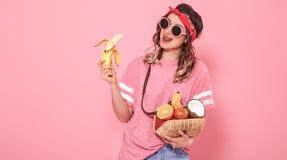 Retrato de una muchacha con la comida sana, frutas, en un fondo rosado imagen de archivo