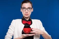 Retrato de una muchacha con la taza roja en sus manos Imagen de archivo libre de regalías