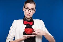 Retrato de una muchacha con la taza roja en sus manos Fotografía de archivo