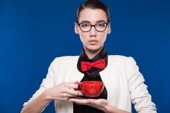Retrato de una muchacha con la taza roja en sus manos Imagenes de archivo