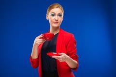 Retrato de una muchacha con la taza roja en sus manos Fotos de archivo