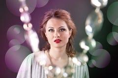 Retrato de una muchacha con los labios rojos en un vestido gris Imagenes de archivo