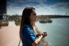 Retrato de una muchacha con un móvil en manos cerca de Sava River, costa de Belgrado, Serbia Fotografía de archivo libre de regalías