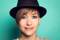 Retrato de una muchacha con un sombrero sonriente en un fondo azul Foto de archivo libre de regalías
