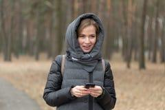 Retrato de una muchacha con un teléfono en la naturaleza Imágenes de archivo libres de regalías