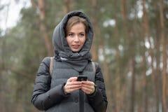 Retrato de una muchacha con un teléfono en la naturaleza Foto de archivo libre de regalías