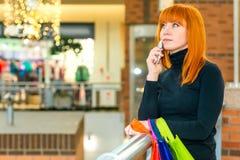 Retrato de una muchacha con un teléfono y un bolso Foto de archivo