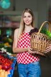 Retrato de una muchacha con una cesta de verduras Imagenes de archivo