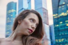 Retrato de una muchacha contra la ciudad de la tarde Fotos de archivo libres de regalías