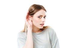 Retrato de una muchacha curiosa joven que intenta oír rumores foto de archivo