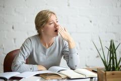 Retrato de una muchacha de bostezo del estudiante en el escritorio Imágenes de archivo libres de regalías