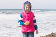 Retrato de una muchacha de cinco años con una manzana en la playa Imagenes de archivo