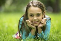 retrato de una muchacha de nueve años que miente en la hierba verde Imagen de archivo libre de regalías