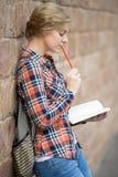 Retrato de una muchacha de pensamiento del estudiante contra la pared de ladrillo, soñando Imagen de archivo libre de regalías