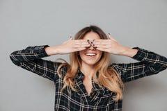 Retrato de una muchacha de risa que la cubre ojos con las manos Imagenes de archivo