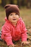 Retrato de una muchacha de un año linda que se arrastra en el parque de la primavera Fotografía de archivo