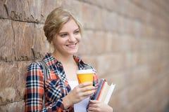 Retrato de una muchacha del estudiante contra la pared de ladrillo Foto de archivo