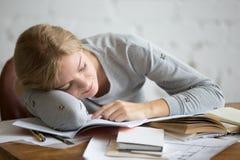 Retrato de una muchacha del estudiante que duerme en el escritorio Imagen de archivo libre de regalías