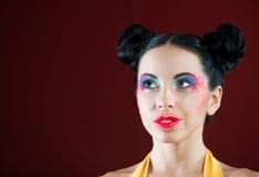 Retrato de una muchacha divertida con maquillaje colorido fotografía de archivo