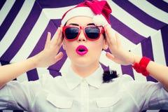 Retrato de una muchacha divertida en el sombrero de Santa Claus y gafas de sol rojas Fotografía de archivo