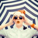 Retrato de una muchacha divertida en el sombrero y las gafas de sol de Santa Claus Fotografía de archivo
