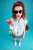 Retrato de una muchacha elegante divertida en las gafas de sol que muestran la lengua Fotografía de archivo