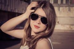 Retrato de una muchacha elegante en gafas de sol en la ciudad imágenes de archivo libres de regalías