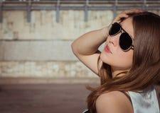 Retrato de una muchacha elegante en gafas de sol en una ciudad fotos de archivo libres de regalías