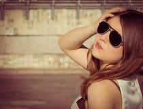 Retrato de una muchacha elegante en gafas de sol en una ciudad imagen de archivo
