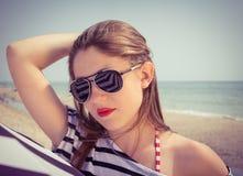 Retrato de una muchacha elegante en una camiseta rayada y las gafas de sol b foto de archivo libre de regalías
