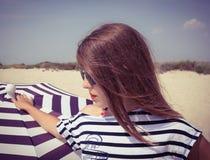 Retrato de una muchacha elegante en una camiseta rayada y las gafas de sol b fotografía de archivo libre de regalías
