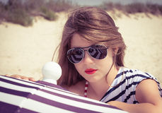 Retrato de una muchacha elegante en una camiseta rayada y las gafas de sol b foto de archivo
