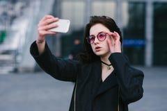 Retrato de una muchacha elegante hermosa joven en los vidrios rosados del inconformista que son fotografiados en su smartphone Imagenes de archivo