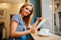 Retrato de una muchacha embarazada joven que se está sentando en un readi del café fotos de archivo libres de regalías