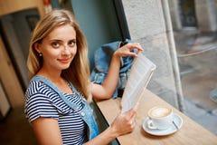 Retrato de una muchacha embarazada joven que se está sentando en un readi del café imagenes de archivo