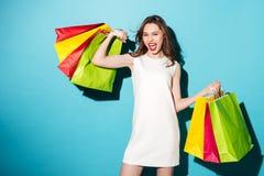Retrato de una muchacha emocionada feliz que sostiene los panieres coloridos Foto de archivo libre de regalías